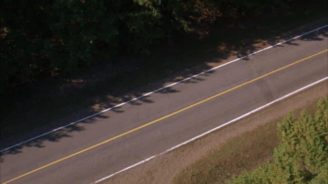 high angle down of country road surrounded by woods and forests. see ford mustang convertible driving through countryside. - ford mustang stock videos and b-roll footage