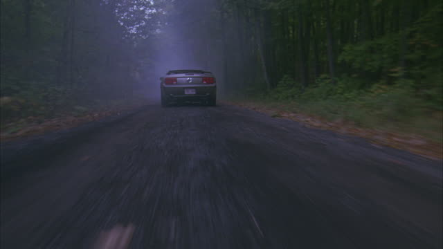 stockvideo's en b-roll-footage met wide angle driving pov down country road, dirt or gravel road, through woods or forest. countryside. ford mustang convertible with massachusetts license plate. could be pursuit or car chase. - grind
