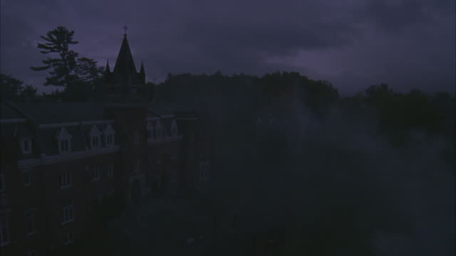 high angle down of college students entering bishop's university building in quebec canada. students carrying umbrellas and wearing uniforms. university or academy. overcast sky and fog blowing across entrance. pan up and across rooftops of university bui - public building stock videos & royalty-free footage