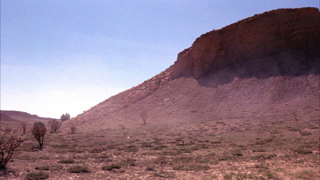 pan left to right of desert mesa or plateau as dust blows by in fg. southwest, rock landscape. 48 fps. - mesa stock videos and b-roll footage