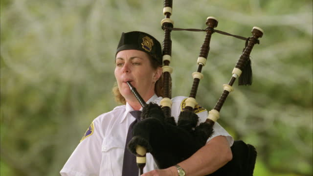 medium angle of female bagpiper. could be a police officer playing at a ceremony such as a funeral. musicians. - bagpipes stock videos & royalty-free footage