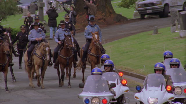 medium angle of police officers on motorcycles and horses and  limos, hearses,  and police cars driving through a cemetery. camera  zooms in to capture police funeral motorcade. flashing lights. bizbars. a news reporter and camera crew broadcast next to t - funeral procession stock videos & royalty-free footage