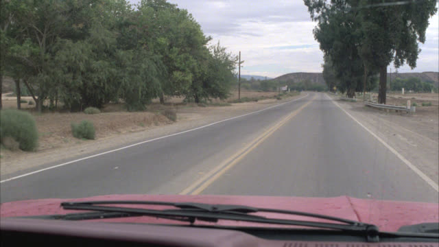 WIDE ANGLE MOVING POV OF TWO LANE RURAL COUNTRY ROAD. A BLACK CONVERTIBLE FORD SHELBY COBRA PASSES. COULD BE COUNTRYSIDE.