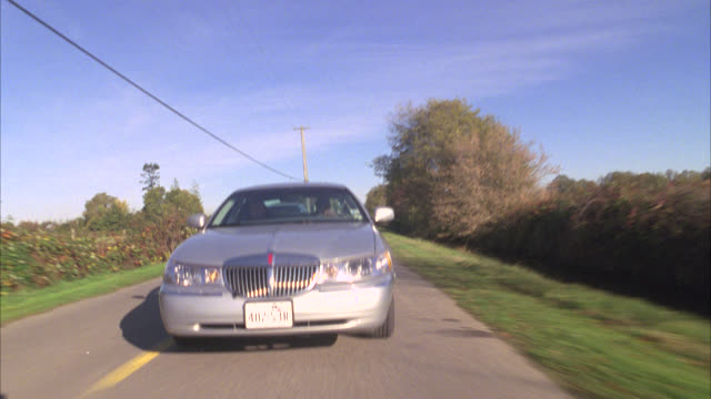 wide angle moving pov from back bumper of car of lincoln town car being chased by two black suvs dodge durangos driving down two lane country road. cars swerves back and forth across road. men lean out windows of suvs and aim guns at lincoln town car. rur - lincoln town car stock videos & royalty-free footage