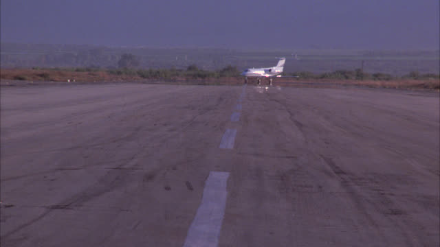 vidéos et rushes de wide angle of private jet, airplane moving down runway towards the camera. jet takes off over camera. airports. corporate jets. tarmacs. learjets. airplane take-offs. - piste d'envol