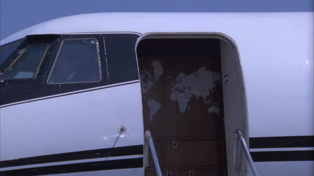 vidéos et rushes de medium angle of open side door of private airplane, plane stopped on tarmac. could be corporate jet. learjet. airports. - piste d'envol