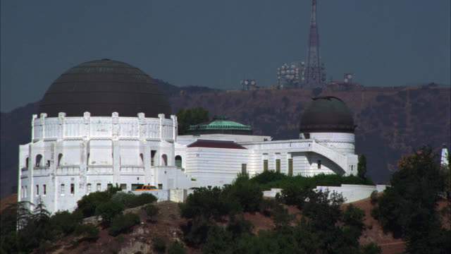 "aerial of griffith park or los angeles observatory with large black domes on bluff or cliff. camera pans over observatory to ""hollywood"" sign and radio towers on hill. scattered green trees and vegetation. - hollywood sign stock videos & royalty-free footage"