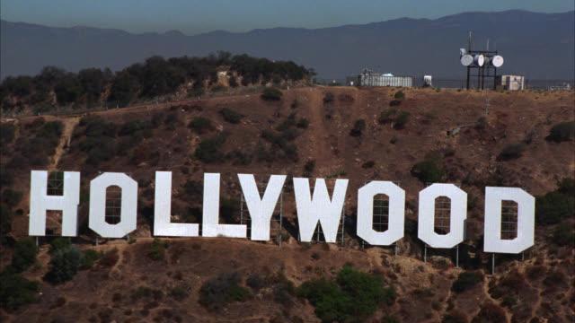 vídeos de stock, filmes e b-roll de aerial of hollywood sign on mt. lee near  radio antenna tower. san gabriel mountains in bg. - hollywood califórnia
