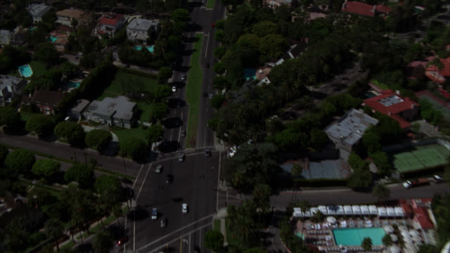 aerial of beverly hills hotel and surrounding residential area. hotel is light pink with red tiled roof, multiple wings, swimming pool and tennis courts. camera flies over sunset boulevard, showing upper-class houses and mansions. - sunset boulevard stock-videos und b-roll-filmmaterial