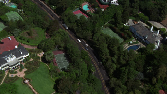 aerial of upper-class residential area in beverly hills along sunset boulevard. houses or  mansions with lawns, swimming pools and tennis courts. estates. - beverly hills california stock videos and b-roll footage