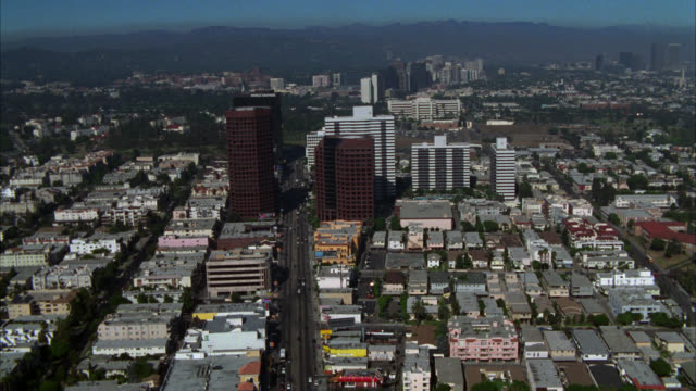 "aerial of business district of los angeles or century city. various office buildings, multi-story buildings, apartment buildings, and high rise buildings. multi-story glass building with sign reading ""world savings."" cars on street below.  mountains in th - ビバリーヒルズ点の映像素材/bロール"