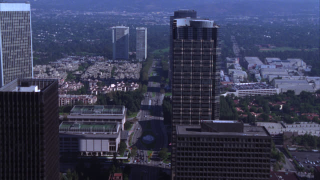 aerial of golf course near century city. camera pans up to century city skyline. multi-story glass office building and high rise buildings. sun america building, fox plaza building, and century city twin tower. fountain in front of abc entertainment cente - century city stock videos & royalty-free footage