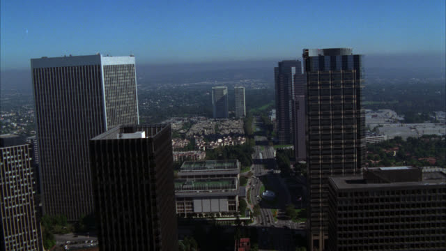 aerial of century city twin towers behind abc entertainment center in century city. various glass office buildings, multi-story buildings and apartment buildings. high rises.. mountains in bg. - century city stock videos & royalty-free footage