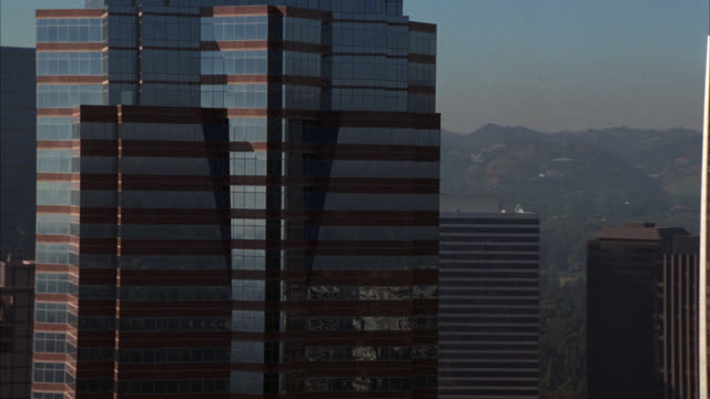 aerial of fox plaza building in century city. glass high-rise building. century city twin towers behind abc entertainment center. mountains in background. office buildings. - beverly hills california stock videos & royalty-free footage