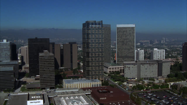 aerial of business district in century. sun america building and century city twin towers behind abc entertainment center. various office buildings, multi-story buildings, and apartment buildings in surrounding area. fox plaza building. mountains in bg. - century city stock videos & royalty-free footage