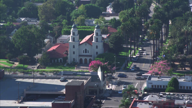 vídeos de stock e filmes b-roll de aerial of beige church with red tiled roof and two towers in santa monica or westwood area. could be mission. palm trees line streets where light traffic drives. homes, houses or buildings in surrounding residential area. yard with swimming pools. - santa monica