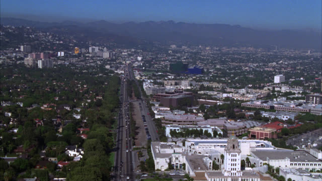 AERIAL OF BEVERLY HILLS OR WEST HOLLYWOOD RESIDENTIAL AREA. CARS TRAVEL OR DRIVE ON STREET BELOW. VARIOUS HOMES, HOUSES, APARTMENT BUILDINGS, AND OFFICE BUILDINGS. MOUNTAINS IN BACKGROUND. PACIFIC DESIGN CENTER IN BG.