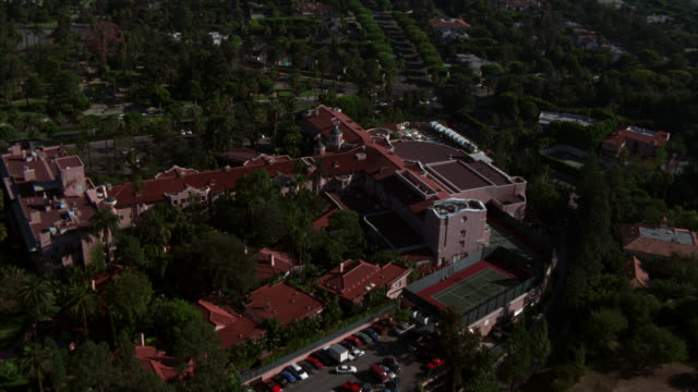 aerial of beverly hills hotel with multiple wings. light pink colored multi-story hotel with red tiled roof. large swimming pool and tennis court to side of hotel. green trees and vegetation surround area. century city in bg.. - beverly hills hotel stock videos and b-roll footage