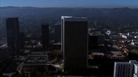 aerial of century city twin towers behind abc entertainment center in century city. fox plaza building. sun america building in bg. various office buildings, multi-story buildings, glass high rises, and apartment buildings in business district. streets or - century city stock videos & royalty-free footage
