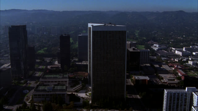 aerial of century city twin towers behind abc entertainment center in century city. fox plaza building. sun america building in bg. various office buildings, multi-story buildings, glass high rises, and apartment buildings in business district. streets or - century city stock-videos und b-roll-filmmaterial