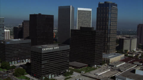 """aerial of business district of century city. various multi-story, office, and high rise buildings. sign on one building read """"century city."""" sun america building, century city twin towers buildings, and fox plaza building. - century city stock videos & royalty-free footage"""