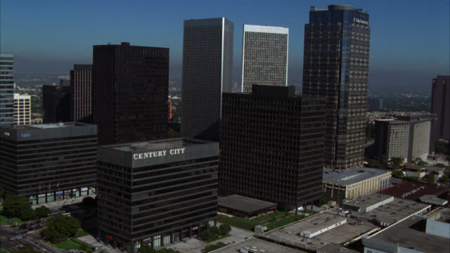"aerial of business district of century city. various multi-story, office, and high rise buildings. sign on one building read ""century city."" sun america building, century city twin towers buildings, and fox plaza building. - century city stock-videos und b-roll-filmmaterial"