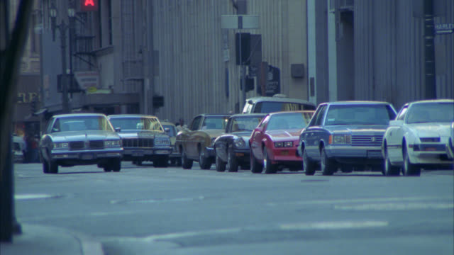 wide angle of cars driving on city street in downtown los angeles. multi-story office buildings in bg. matching r1388-3 r1388-4 - 1985年点の映像素材/bロール