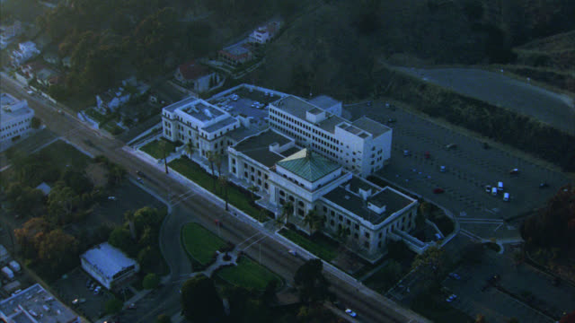 aerial of large, white, multi-story building with columns or pillars. could be courthouse or government building. undeveloped land and mountains with green trees behind building. various buildings, office buildings, and houses in surrounding area of ventu - santa barbara bildbanksvideor och videomaterial från bakom kulisserna