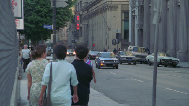 vídeos de stock e filmes b-roll de people walking on sidewalk, cars driving on city street, could be in downtown los angeles. multi-story office buildings on right side of street. pedestrians. - 1985