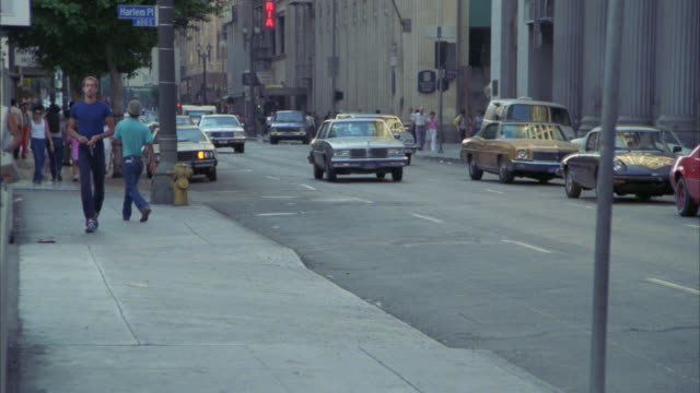 pedestrians, people walking on sidewalk, cars driving on city street, could be in downtown los angeles     multi-story office buildings on right side of screen. - anno 1985 video stock e b–roll