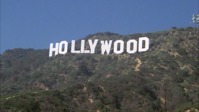 """zoom in on """"hollywood""""  sign and the hollywood hills. graffiti visible on letters of sign. - hollywood california stock videos & royalty-free footage"""