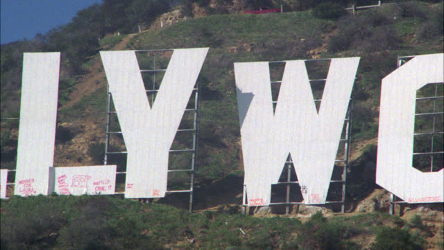 """close angle of """"hollywood"""" sign in the hollywood hills. people walking at base of letters. - hollywood california stock videos & royalty-free footage"""