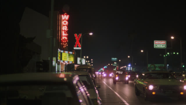 WIDE ANGLE OF CARS DRIVING DOWN LOS ANGELES STREET. STRIP CLUB AND CAR DEALERSHIP ON OPPOSITE SIDES OF STREET. CAMERA PANS LEFT TO RIGHT FOLLOWING SPEEDING CAR DOWN STREET. NEON SIGNS.