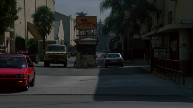 pan right to left as gray two-door mercedes benz drives into burbank studios barham gate. cars driving down barham. palm trees next to sound stages. movie studio back lots. multiple takes. - 1986 stock videos and b-roll footage