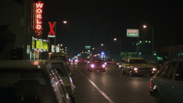vidéos et rushes de wide angle of cars driving down los angeles street. strip club and car dealership on opposite sides of street. camera pans left to right following speeding car down street. neon signs. city bus. - peep show