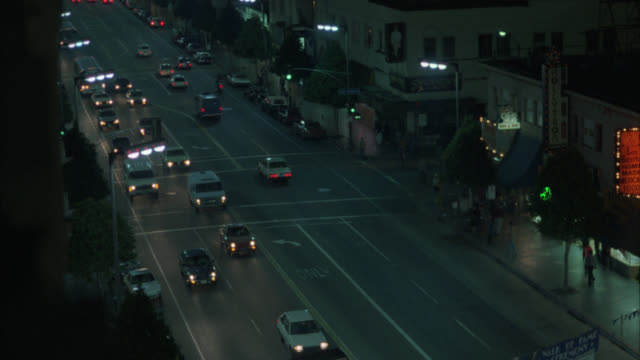 vídeos de stock e filmes b-roll de high down angle of cars driving down hollywood blvd. neon signs. headlights. - 1985