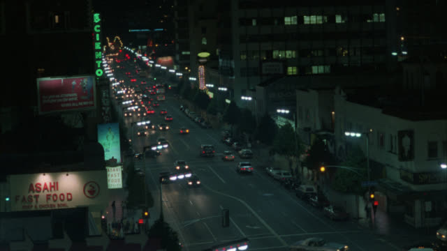 high down angle of cars driving down hollywood blvd. neon signs. headlights. city buses. - anno 1985 video stock e b–roll