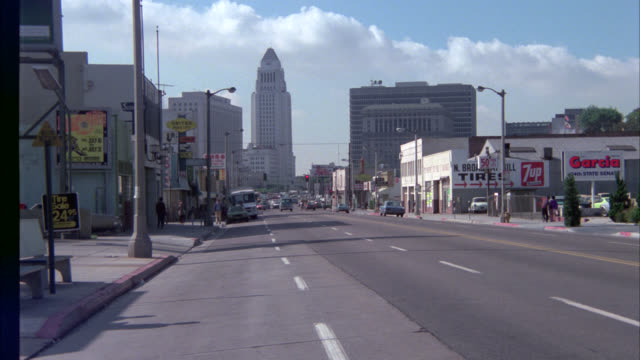 wide angle of cars driving on downtown los angeles street. camera pans left to right as sedan drives by. city hall in bg. - anno 1975 video stock e b–roll