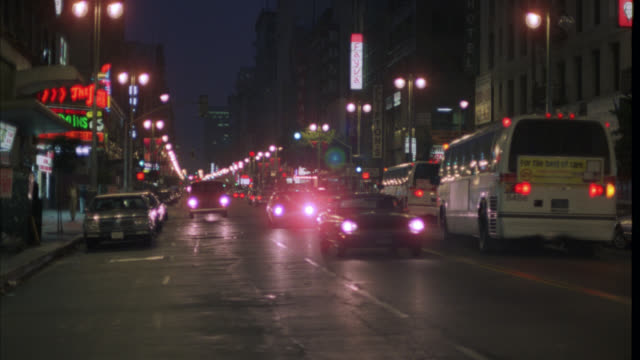 vidéos et rushes de wide angle of car and van driving down hollywood boulevard. busy city street with cars, trucks, and city buses. camera pans left to right following cars. neon signs and marquees. - hollywood california