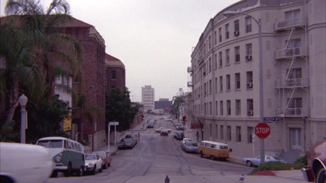 wide angle of cars and vans parked on residential street. apartment buildings line street. cars drive on street. - anno 1975 video stock e b–roll