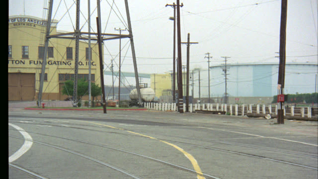 """pan left to right at swat van drives down street by los angeles harbor shipyard or cranes. cotton fumigating building in bg. van parks at entrance to warehouse in front of ship with """"hawaiian legislator"""" written on it. bridge in bg. - legislator stock videos & royalty-free footage"""