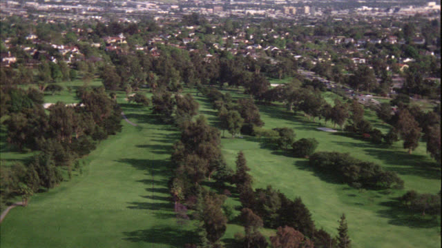 aerial of los angeles skyline. skyscrapers, high rises, and office buildings. camera pans left to right and down to baseball game in progress. baseball field and diamond at country club near golf course. park, residential area, and neighborhood. - clubhouse stock videos & royalty-free footage