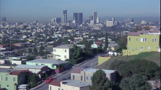 stockvideo's en b-roll-footage met wide angle of los angeles city skyline with high rises, skyscrapers, and office buildings. residential area with trees in the fg. mountains in ng. camera pans right to left to follow car down street. - 1977