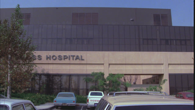 "WIDE ANGLE OF MULTI-STORY HOSPITAL BUILDING. ""HOSPITAL"" SIGN ON SIDE OF BUILDING. CARS PARKED IN PARKING LOT IN FG."