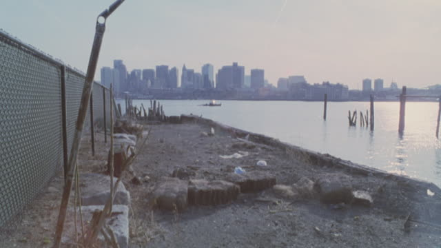 pan left to right of harbor, boat moves through water. abandoned rundown dockyard with construction equipment, debris. city skyline and downtown. waterfronts. new england. - pier stock videos & royalty-free footage