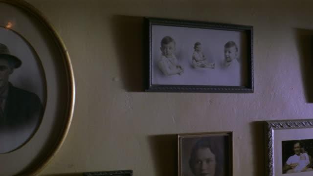 vídeos de stock, filmes e b-roll de medium angle of framed photographs on wall. vintage photographs of family members. - imagem