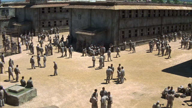 WIDE ANGLE OF PRISONERS IN PRISON YARD. PRISONERS WEAR UNIFORMS. MEN STAND TALKING IN GROUPS. SOME INMATES PLAY SOCCER IN BG. OTHER MEN LIFT WEIGHTS IN RIGHT FG. CORRECTIONAL FACILITY. STATE PENITENTIARY. COULD BE USED FOR ANY 1940'S PRISON IN THE SOUTHWE