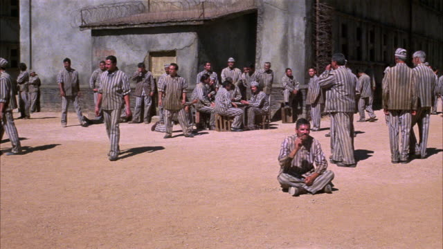 wide angle of prisoners in prison yard. prisoners wear uniforms. men stand talking in groups. some inmates play soccer in bg. correctional facility. state penitentiary. could be used for any 1940's prison in the southwest. - 1940 1949 stock-videos und b-roll-filmmaterial