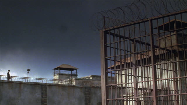 wide angle of prison. prison guards with guns pace on guard wall. metal cage with barbed wire fence visible in front of building. sky has dark clouds. weapons. men. correctional facility. state penitentiary. could be used for any 1940's prison. in the sou - 1940 1949 stock-videos und b-roll-filmmaterial