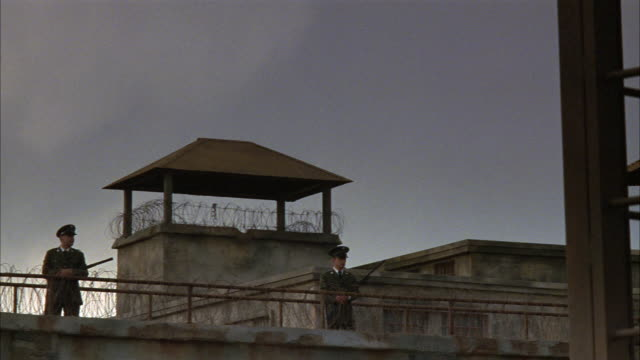 stockvideo's en b-roll-footage met medium angle of prison. pov begins at barbed wire fence attached to metal cage and pans left to prison guards with guns at guard wall. guard tower visible in bg. weapons. men. correctional facility. state penitentiary. could be used for any 1940's prison. - 1940 1949